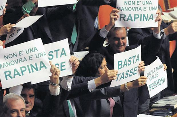 Members of Northern League Party (above) hold placards to protest against austerity package in the upper house of parliament in Rome yesterday