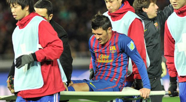 Barcelona's David Villa (C) is stretchered off during their semi-final football match against Al Sadd at the Club World Cup. Photo: Getty Images