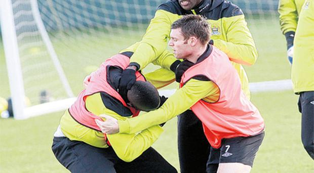 James Milner and Yaya Toure restrain team-mate Mario Balotelli during a Manchester City training session yesterday