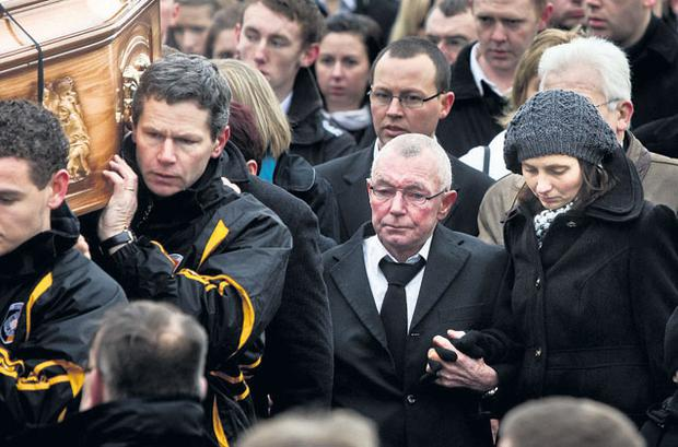 Members of the Crossmaglen Rangers GAA club carrying the remains of James Hughes to St Patrick's Church in the town yesterday. The mourners were led by his father James Hughes snr and partner Genny