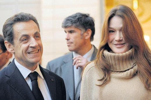 France's president Nicolas Sarkozy and his wife Carla Bruni-Sarkozy attend a Christmas party at the Elysee Palace in Paris on Wednesday. The financial crisis and resulting austerity measures have given the French president a huge task to get re-elected in May. His main rival is currently leading in opinion polls.