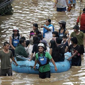 Volunteers use a boat to ferry residents to safer grounds following severe flooding in Cagayan de Oro (AP)