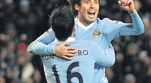 Sergio Aguero celebrates with match-winner David Silva as Manchester City beat Arsenal 1-0 yesterday