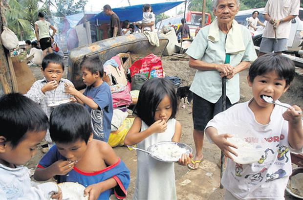 Flood victims eat a meal in a makeshift shelter along a road in Iligan city in southern Philippines yesterday, where up to 50 victims were buried in a mass funeral as undertakers struggle to cope