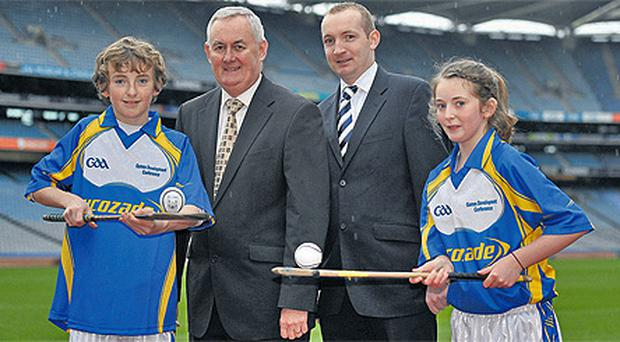 GAA president Christy Cooney alongside Jim Geraghty, Senior Brand Manager of Lucozade Sport, with Barry Neville, age 14, left, and Clare Nulty, age 13, from Castleknock GAA Club at the GAA Games Development Conference Launch in Croke Park yesterday