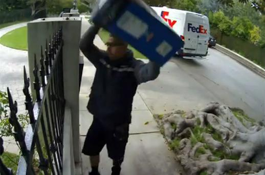 The FedEx delivery man can be seen tossing the Samsung branded box over a fence. Photo: YouTube