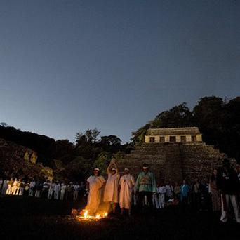 People watch as Mayan priests participate in a ceremony in Mexico (AP)