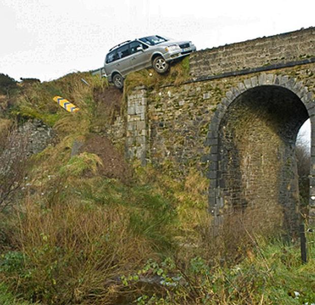 The couple's car perched dangerously on the edge of the bridge
