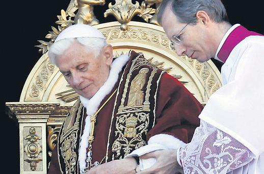 Pope Benedict leaves the balcony after delivering his Christmas Day message yesterday. The Pope's anti-violence message came as news emerged that five bombs had been detonated at a chruches in Nigeria, killing 39
