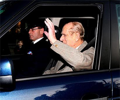 The Duke of Edinburgh waves as he is driven away from hopsital