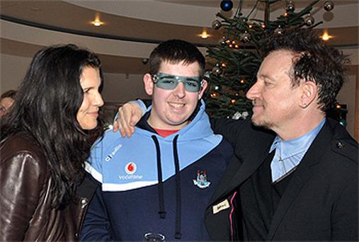 Bono lets a young fan try on his shades at the Leopardstown Races yesterday as wife Ali looks on