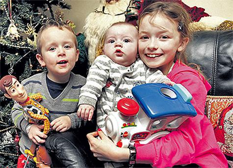 Ellen Kellet (10) and brothers Thomas (3) and Eric (six months) opened their Christmas presents while their hero mum, Vivienne, rested in Tallaght Hospital, Dublin
