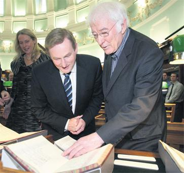 Seamus Heaney shows Taoiseach Enda Kenny some of the papers he has gifted to the National Library of Ireland