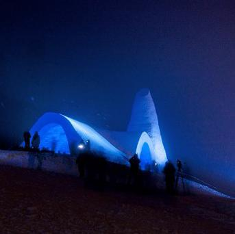 Visitors pass by a blue-lit church built of snow during its opening in Mitterfirmiansreut, Germany (AP)
