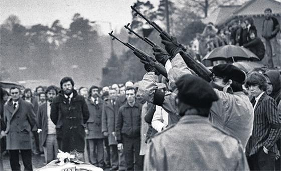 Gunmen fire a volley of shots over the coffin of Bobby Sands in 1981