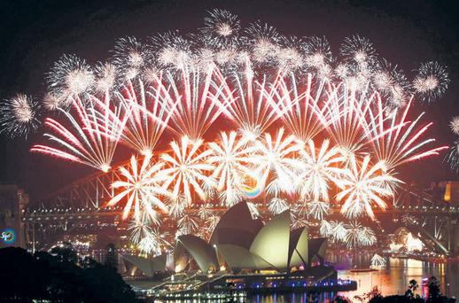 LIGHTING UP: Fireworks explode over the Sydney Harbour Bridge and Opera House during a pyrotechnic show to celebrate the New Year. Photo: Daniel Munoz