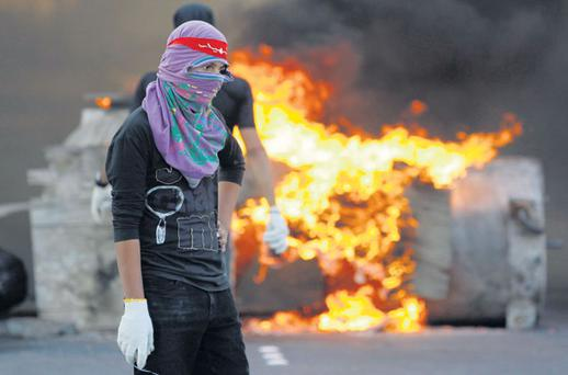 A protester holding stones stands next to a blaze during police clashes in the village of Sitra, south of the capital Manama, Bahrain.