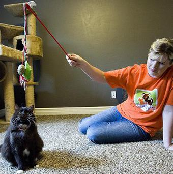 Janita Coombs plays with her cat Andrea after the animal survived two attempts to put her to sleep (AP)