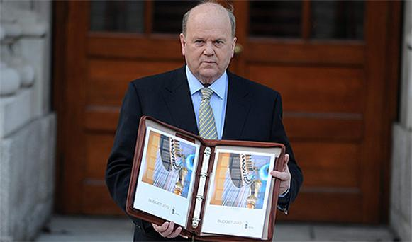 Finance Minister Michael Noonan poses with the Budget for 2012 outside Leinster House