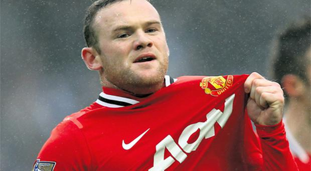 Wayne Rooney gestures with his club badge after giving Manchester United the lead during yesterday's FA Cup third round match against Manchester City