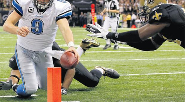 Matthew Stafford of the Detroit Lions dives in for a touchdown despite the efforts of New Orleans Saints' Roman Harper and Will Smith during their Wild Card play-off game in New Orleans on Saturday