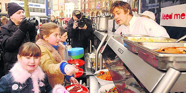 Celebrity Chef Jamie Oliver serves up a healthy school dinner to pupils from Ealdham Primary School, Greenwich, in Leicester Square, central London