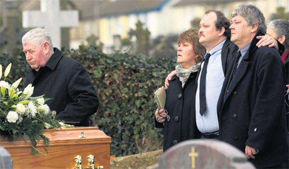 Gerard Vollrath (centre) with his arms around his sister, Anna Kirk, and brother, Paul, as they follow the coffin of their mother Vera Vollrath