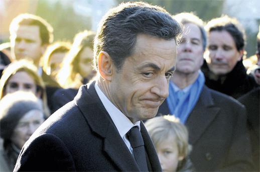 French President Nicolas Sarkozy pays his respects at the grave of former French prime minister Michel Debreer
