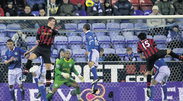 Edin Dzeko heads home the winner for Manchester City at the DW Stadium