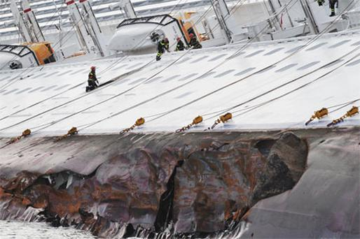 Rescuers work on the cruise ship Costa Concordia as lies stricken off the shore of the island of Giglio. Photo: Getty Images