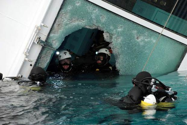 Carabinieri scuba divers swim close to the Costa Concordia cruise ship, off the tiny Giglio island, Italy. The $450 million Costa Concordia was carrying more than 4,200 passengers and crew when it slammed into well-marked rocks off the island of Giglio.