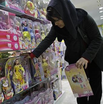 An Iranian shopkeeper arranges a display of dolls at her shop in Tehran (AP)
