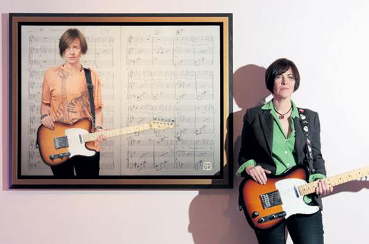 Singer Eleanor McEvoy poses with a Fender Telecaster guitar beside the portrait of her painted by Robert Ballagh, which now hangs in the National Concert Hall. JASON CLARKE PHOTOGRAPHY