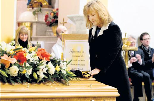SOLEMN THOUGHT: Anne Harris, deputy editor of the 'Sunday Independent', lays a hand on the coffin of her late husband, Aengus Fanning, on Friday, with Charles Lysaght, and Dion and Evan Fanning in background. Photo: David Conachy