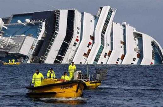 Oil recovery workers pass in front of the Costa Concordia cruise ship. Photo: Reuters