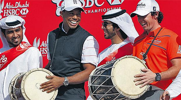 Tiger Woods and Rory McIlroy bang the drum ahead of the 2012 Abu Dhabi Golf Championship alongside a traditional Emirati Ayala dance troupe yesterday