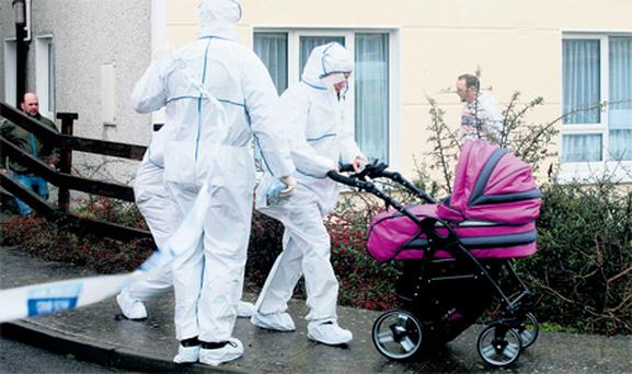 Garda forensic officers help with the evacuation of residents in the street where Jason Ryan was stabbed to death