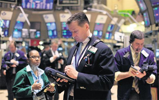 Traders work on the floor of the New York Stock Exchange, yesterday. US stocks rallied, erasing an earlier loss in the Standard & Poor's 500 Index, as the Federal Reserve said interest rates will remain low until late 2014 and Apple rallied after earnings more than doubled