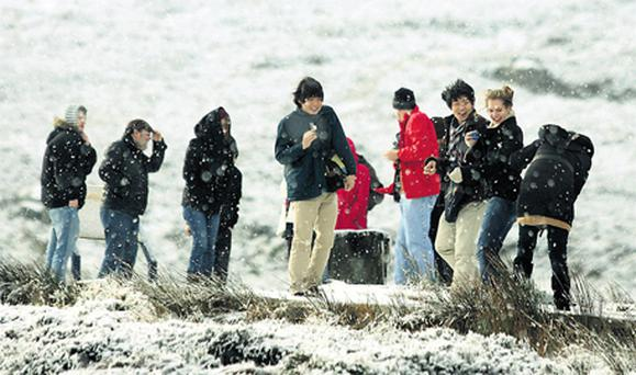 Tourists on a coach tour of the Wicklow Mountains stop to enjoy the sights and snow in the Wicklow Gap yesterday