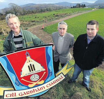 Kilgarvan GAA Club chairman Tom Randles with fellow officers Jerh Lyne and Thomas O'Reilly at the Kilgarvan GAA Club field yesterday. Behind them is part of the adjoining presbytery site