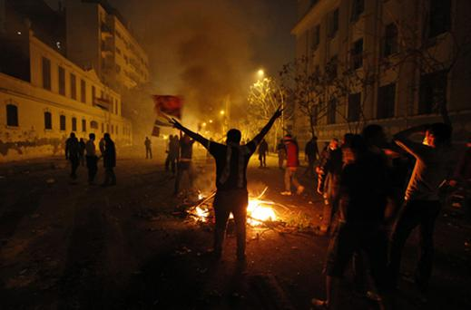 An Egyptian protestor flashes the victory sign as he stands near a bonfire during clashes with the security forces near the interior ministry in downtown Cairo. Photo: PA