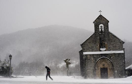 A man walks as snow and freezing wind billows across the region, in Roncesvalles, northern Spain. Photo: Getty Images
