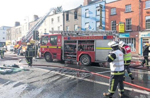 Members of the fire service at the scene of the blaze on Camden Street, Dublin, yesterday
