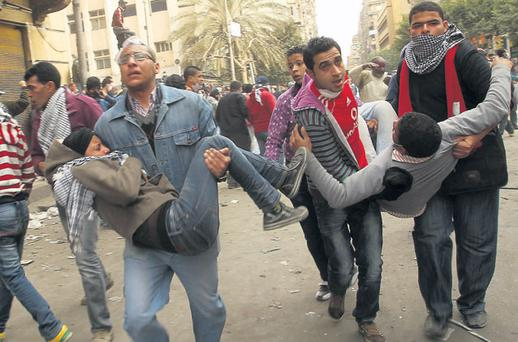 Wounded protesters are evacuated during clashes with security forces near the Interior Ministry in Cairo yesterday