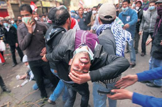 ANGER RISING: A wounded protester is carried during clashes near the Interior Ministry in Cairo, Egypt