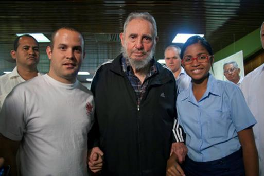 Former Cuban leader Fidel Castro stands with unidentified people at the presentation of his biography