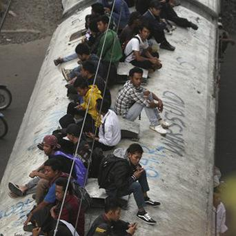Brooms covered in putrid liquid are to be used in Indonesia to deter people from travelling on train roofs (AP)