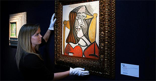 An employee holds a Pablo Picasso's 'Femme au fauteuil' at Christie's auction house in London
