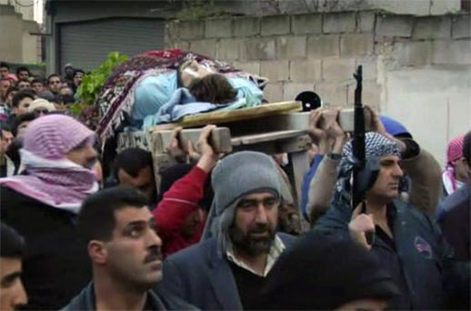 A still from amateur footage shows a dead man carried outside in a funeral procession in Homs, Syria. Photo: AP