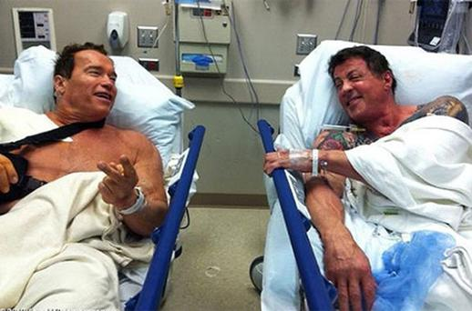 Arnold Schwarzenegger and fellow actor Sylvester Stallone on neighbouring hospital gurneys in a Los Angeles hospital. Photo: Reuters